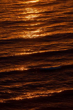 Golden evening sunlight reflecting in the dark water, texture close-up. Summer sunset. Baltic sea, Denmark