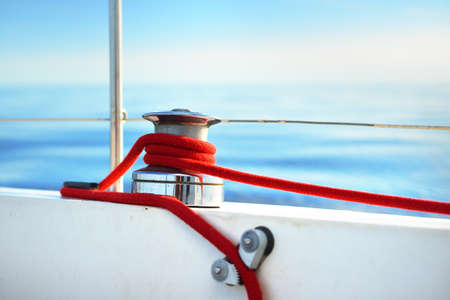 White yacht sailing at sunset. A red winch close-up. Waves and clouds. Baltic sea
