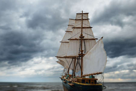 Antiquarian wooden scale model of the clipper tall ship, close-up. Dramatic sky, dark stormy clouds and sea. Traditional craft, souvenir, hobby, collecting, vintage, modeling. Zero waste concept