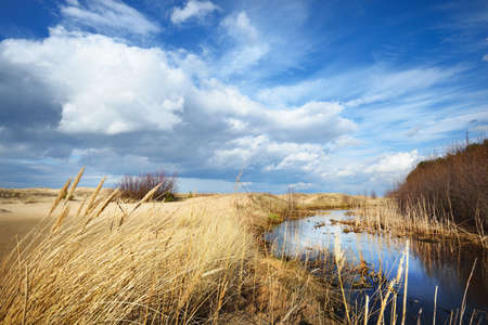 Crystal clear water and sandy shore of the Baltic sea on a sunny spring day. Shallow water. Dramatic cloudscape. Latvia. Seasons, climate change, weather