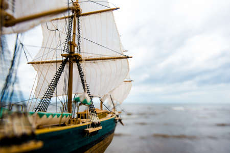Scale model of a wooden sailing ship on the coast of the Baltic Sea on a cloudy spring day
