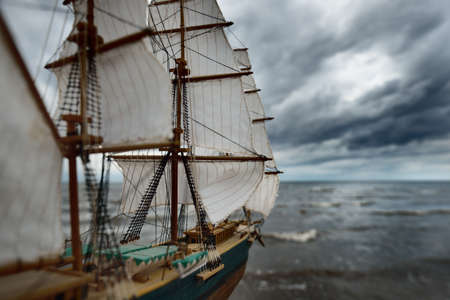 Antiquarian wooden scale model of the clipper tall ship, close-up. Dramatic sky, dark stormy clouds and sea. Traditional craft, souvenir, hobby, collecting, vintage, modeling. Zero waste concept Stock Photo