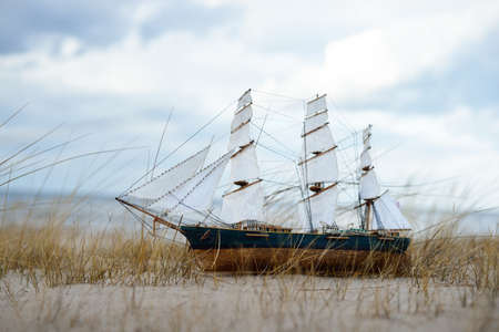 Antiquarian wooden scale model of the clipper tall ship, close-up. Dramatic sky, sandy shore (sand dunes) of the Baltic sea. Traditional craft, souvenir, toy, hobby, vintage, collecting, modeling