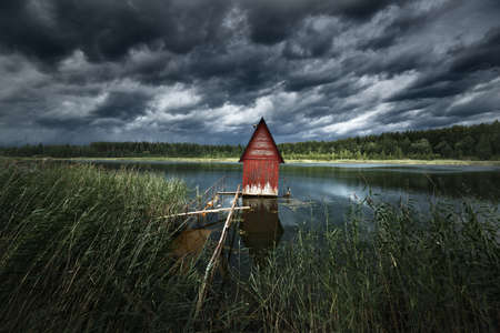 A small red decorative wooden house (log cabin) near the lake and the forest, close-up, Latvia. Dramatic clouds before the thunderstorm. Idyllic rural scene