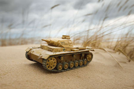 German WWII Panzer III scale model toy tank close-up. Sand dunes of the Baltic sea in the background. Modeling, collecting, education, history concepts