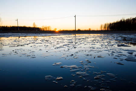Spring landscape. A flood on the street at sunset. Reflection on the water. Ice fragments close-up. Riga, Latvia 写真素材