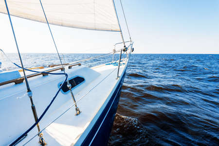 White yacht sailing in an open Baltic sea on a clear day. A view from the deck to the bow and sails. Waves and water splashes. Latvia