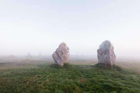 Menhir alignment view at Camaret sur mer at sunrise. Strong morning fog. Brittany, France