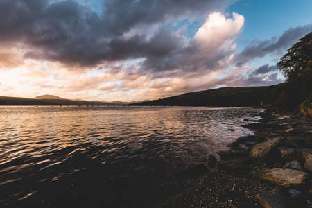 Rocky lake shore under the stormy evening sky after the rain. Dramatic sunset cloudscape. Gare Loch, Rhu, Scotland, UK. Travel destinations, vacations, leisure activity concepts
