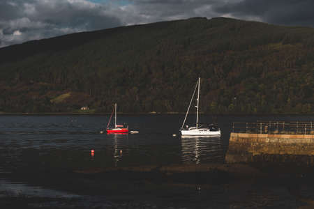 Sailing boats anchored on mooring near the shore of Loch Fyne, close-up. Dramatic sky. Majestic forest hills in the background. Inveraray, Argyll and Bute, Scotland, UK. Travel destinations theme