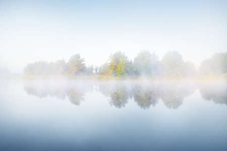 Picturesque scenery of the forest lake in a thick white fog. Reflections on the water. Pure golden sunlight. Atmospheric landscape. Fall season. Nature, ecology, environmental conservation in Europe