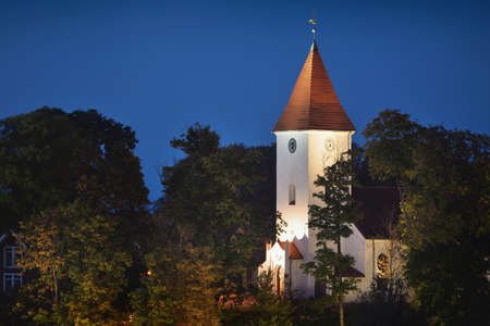 Illuminated cityscape at night, church tower and spire close-up. Old town of Talsi, Latvia. Travel destinations, vacations, tourism, landmarks, sightseeing, culture and religion