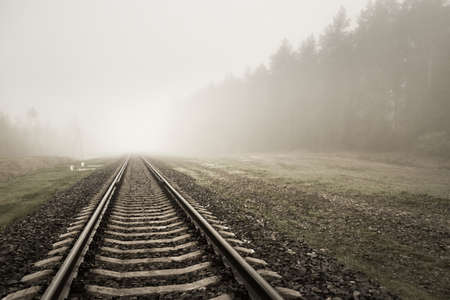 Railroad track in a thick white fog, forest in the background. Concept landscape. Freight and passenger transportation, industry, business, communications, environmental damage. Sepia, monochrome