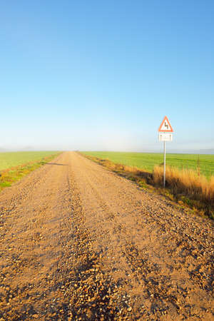 An old country asphalt road through the village in a fog. Street sign close-up. Clear blue sky. Rural scene. Transportation, countryside, road trip, driving. Symbol, copy space, graphic resources