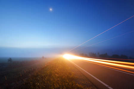 Panoramic view of the empty highway through the fields in a fog at night. Moonlight. Sunrise. Europe. Transportation, logistics, travel, road trip, freedom, driving. Motion blur effect. Rural scene 스톡 콘텐츠