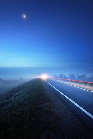 Panoramic view of the empty highway through the fields in a fog at night. Moonlight, clear sky. Sunrise. Europe. Transportation, logistics, travel, road trip, freedom, driving. Rural scene 스톡 콘텐츠