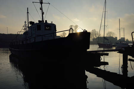Old blue tug boat moored to a pier, close-up. Yacht club at sunset. Soft evening light. Nautical vessel, transportation, sport, amateur recreational sailing, fishing, industry, traditional craft