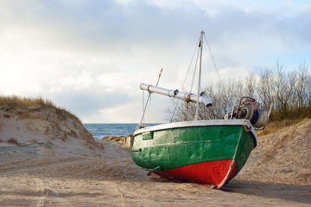 Old green fishing boat standing on land in a small village, sandy shore of the Baltic sea. Jurmalciems, Latvia. Vessel, transportation, logistics, industry, fishing, farm, food production. Rural scene