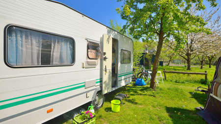 White caravan trailer parked on a green lawn under a tree in a camping site. Spring landscape. Transportation, road trip, vacations, tourism, freedom, leisure activity ,. lifestyle