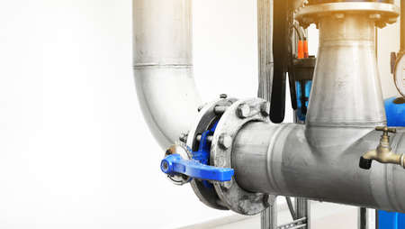 Large industrial water treatment and boiler room. Shiny steel metal pipes and blue pumps and valves with copy space 免版税图像
