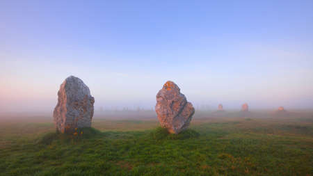 Menhir alignment view at Camaret sur mer in a morning fog at sunrise. Brittany, France. Golden light. Panoramic picturesque scenery. Travel destinations, national landmarks. sightseeing, history