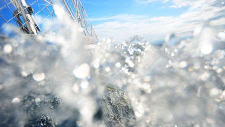 View from the deck of a sailboat close to the surface of the sea with waves and water splashes. Transportation, nautical vessel, cruise, sport, regatta, recreation, leisure activity