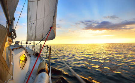 View from the deck of a yacht sailing in calm baltic sea at the evening. Clear ky with glowing golden clouds. Transportation, nautical vessel, cruise, sport, regatta, recreation, leisure activity
