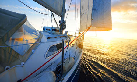 View from the deck of a yacht sailing in calm baltic sea at sunset. Clear sky with glowing golden clouds. Transportation, nautical vessel, cruise, sport, regatta, recreation, leisure activity