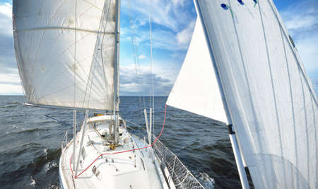 Sloop rigged yacht sailing in an open sea. Top down (high angle) view from a bow with mast and full sails. Transportation, nautical vessel, cruise, sport, regatta, recreation, leisure activity