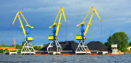 Port cranes next to a pile of coal in a port in Latvia, Baltic sea. Freight transportation, equipment, global communications, logistics, fuel generation, environmental damage