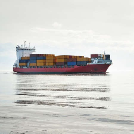 Large cargo container ship sailing in a still sea water on a clear day. Panoramic view. Freight transportation, global communications, logistics, industry, business, economy, environmental damage