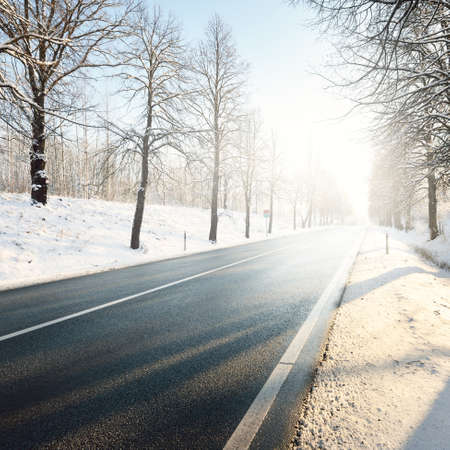 An empty highway (clean asphalt road) through snow-covered forest. Winter rural scene. Travel, Christmas vacations, logistics, dangerous driving, off-road, transportation, winter tires, speed, freedom