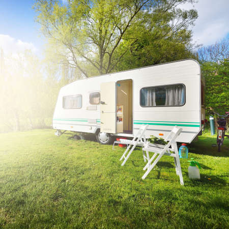White caravan trailer parked on a green lawn in a camping site, wooden chairs close-up. Spring landscape. Transportation, RV, road trip, tourism, freedom, leisure activity, lifestyle. England