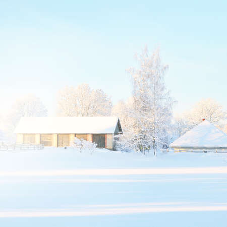 Winter landscape with cozy German style rural cottage in the countryside on a sunny day. Traditional architecture, travel destinations, Christmas vacations, ecotourism, remote places