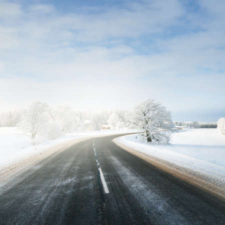 Panoramic view of the clean winding S shape highway through snow-covered field, forest, village. Winter rural scene. Travel, Christmas vacations, logistics, dangerous driving, off-road, transportation