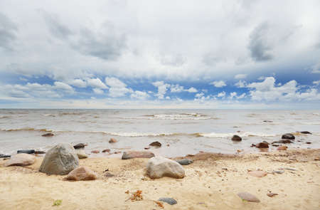 Panoramic view from the rocky Baltic sea shore. Summer. Gulf of Riga, Latvia. Dramatic sky, waves, water splashes. Weather, storm, gale. Vacations, travel destinations, ecotourism. Nature, seascape