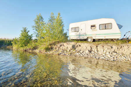 White caravan trailer parked on the rocky river shore on a sunny day. Clear blue sky. Ba; tic states, Europe. Summer vacations, travel, ecotourism, recreation, off-grid camping, road trip, RV