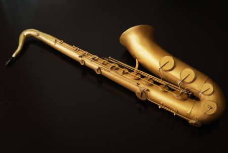 Scale model saxophone isolated on black background. Studio shot. 3d rendering, printing, graphic resources, copy space. Musical instrument, melody, jazz, orchestra, concert, culture. Hobby, collecting 版權商用圖片