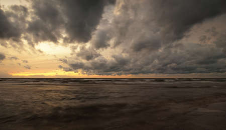 Baltic sea shore after the storm. Dramatic sunset sky, dark glowing clouds, golden sunlight. Waves, splashing water. Picturesque scenery, seascape, cloudscape, nature. Panoramic view, long exposure