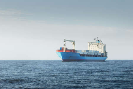 Large blue cargo container ship with a crane sailing in an open sea. USA. Freight transportation, nautical vessel, global communications, logistics, shipping, delivery, industry, commerce, economy Banque d'images