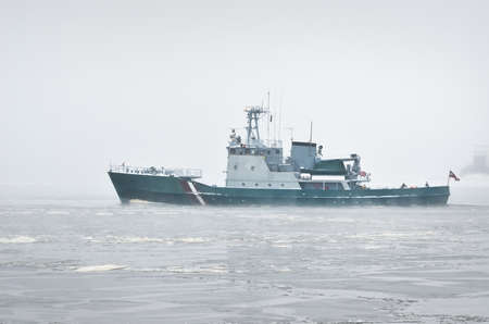 Coast guard ship sailing during the storm. Winter. Fog, waves, rough weather. Baltic sea. Transportation, nautical vessel, international security, global communications, border control, customs Banque d'images