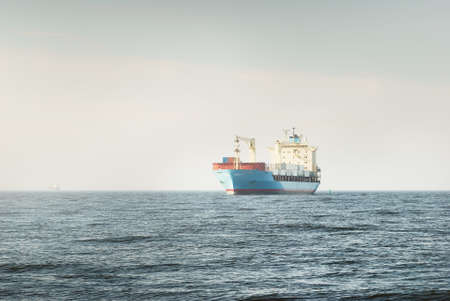 Large blue cargo container ship with a crane sailing in an open sea. USA. Freight transportation, nautical vessel, global communications, logistics, shipping, delivery, industry, commerce, economy