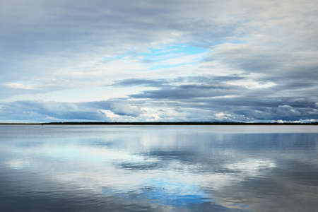 Forest lake with symmetry reflections in crystal clear water, natural mirror. Dramatic sky, ornamental glowing cumulus clouds before the rain. Nature of Scandinavia. Idyllic landscape. Panoramic view Фото со стока
