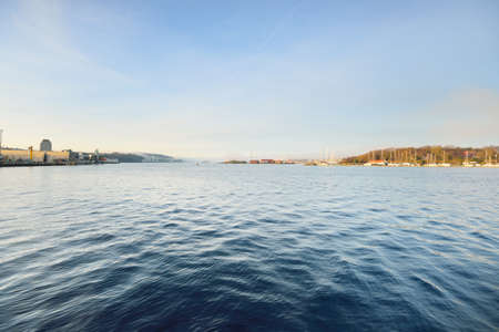 A view of the city from the water. Yachts, port cranes in the background. Stavanger embankment, Norway. Travel destinations, tourism, ferry, cruise, transportation, nautical vessel, economic growth