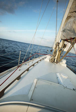 White sloop rigged yacht sailing in the sea at sunset. Clear sky. A view from the deck to the bow, mast, sails. Transportation, travel, cruise, sport, recreation, leisure activity, racing, regatta Foto de archivo
