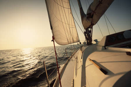 White sloop rigged yacht sailing in an open sea at sunset. Clear sky. A view from the deck to the bow, mast, sails. Transportation, travel, cruise, sport, recreation, leisure activity, racing, regatta Banque d'images