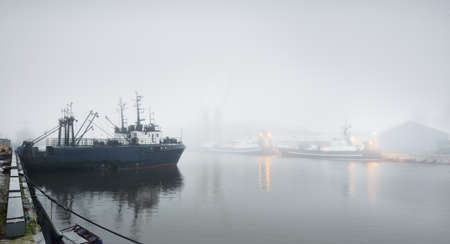 Tugboats and fishing boats (trawlers) moored to a pier in a harbor. Thick white fog. Latvia, Baltic sea. Panoramic view. Service, repair, freight transportation, logistics, industry, commerce Standard-Bild