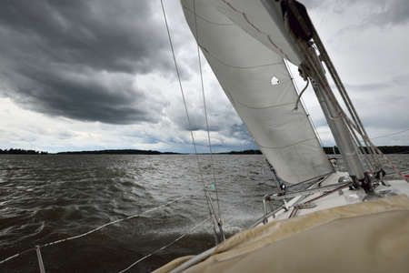 White yacht sailing during the storm. View of the mast, sails, rigging equipment. 32 feet swedish built cruising sailboat. Mälaren lake, Sweden. Summer vacations, recreation, sport, leisure activity