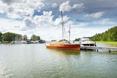 Classic wooden luxury motorboat sailing on a clear day. Stockholm sail club, Mälaren lake, Sweden. Summer vacations, yachting, leisure activity, service, lifestyle, history, retro, private vessel