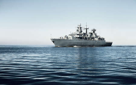 Large grey modern warship sailing in still water. Clear blue sky. Baltic sea, Germany. Global communications, international security, coast guard, borders, navigation, special equipment Banque d'images